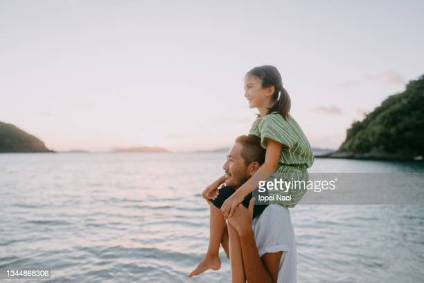 father carrying young daughter on shoulders on beach at sunset - tropical climate stock pictures, royalty-free photos & images