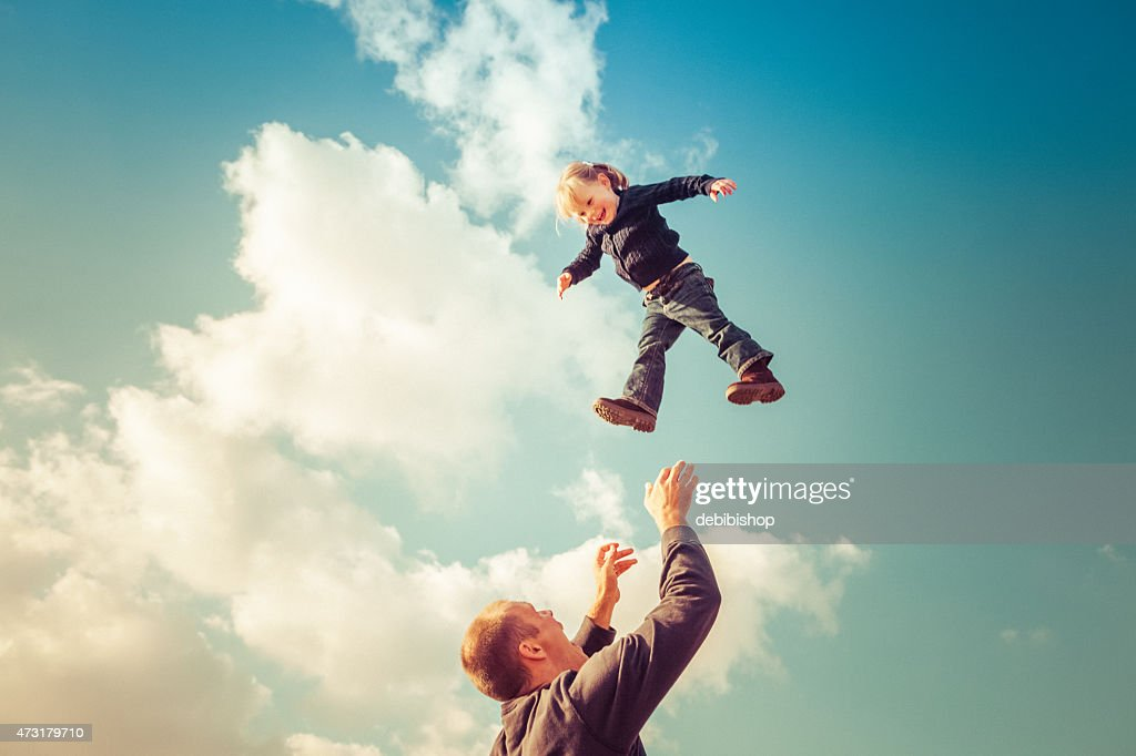 Father catching girl falling from cloudy sky : Stock Photo
