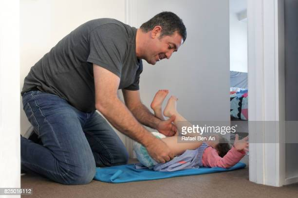 father changes diaper to his daughter - diaper girl photos et images de collection