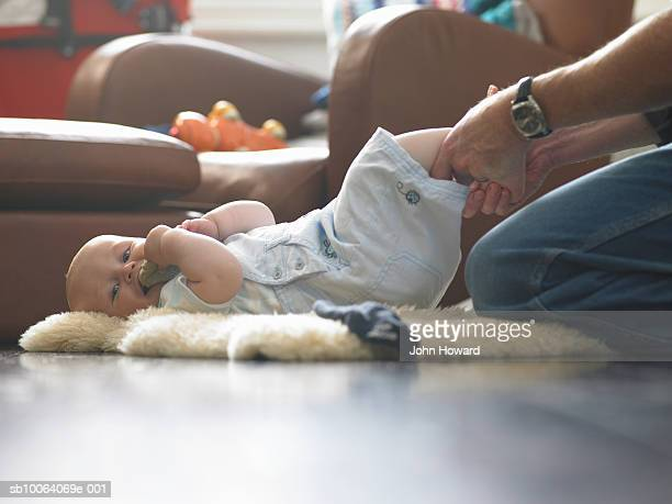 Father changing baby boy (9-12 months) on floor