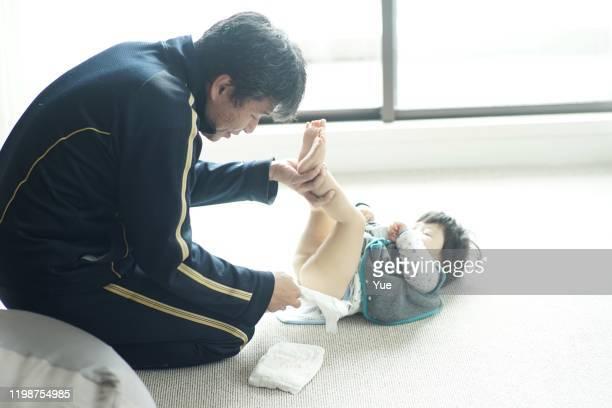 男の子のおむつを交換する父 - オムツを替える ストックフォトと画像