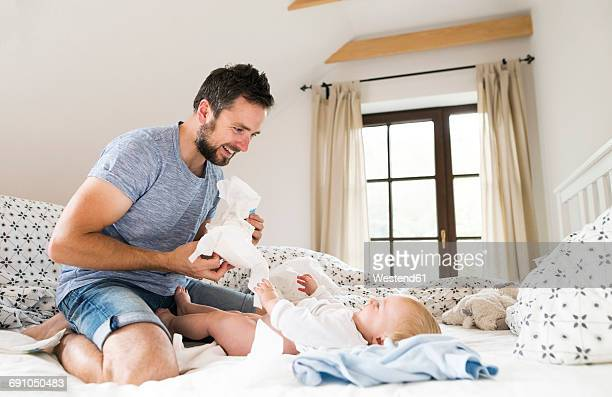 father changing baby's diapers on bed - diaper boy stock photos and pictures