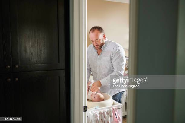 father changing diaper of baby girl - lgbtq  and female domestic life fotografías e imágenes de stock