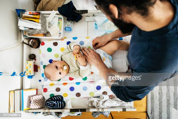 father changing his baby's diaper - diaper stock pictures, royalty-free photos & images