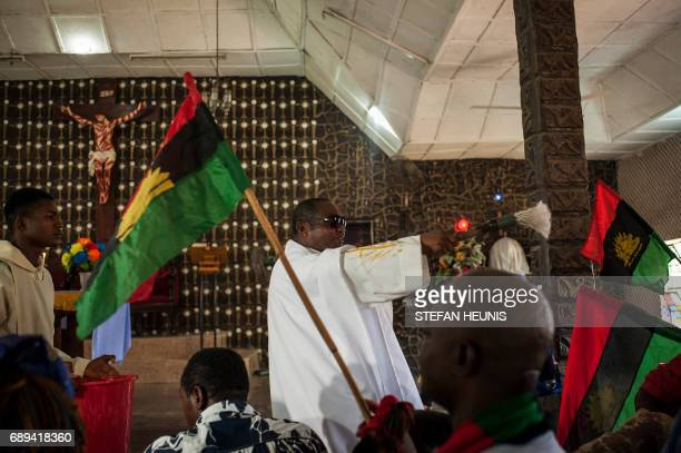 Father Charles Ubawuike blesses members of the parish while waving the Biafran flag during a service at the St Martin Catholic of Tours Church on May...
