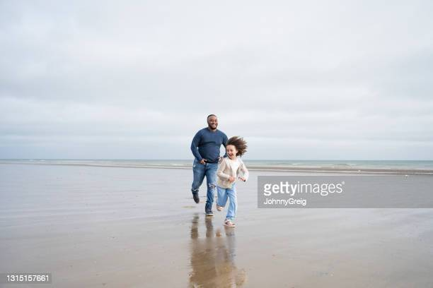 father chasing laughing young daughter on beach at low tide - moving after stock pictures, royalty-free photos & images