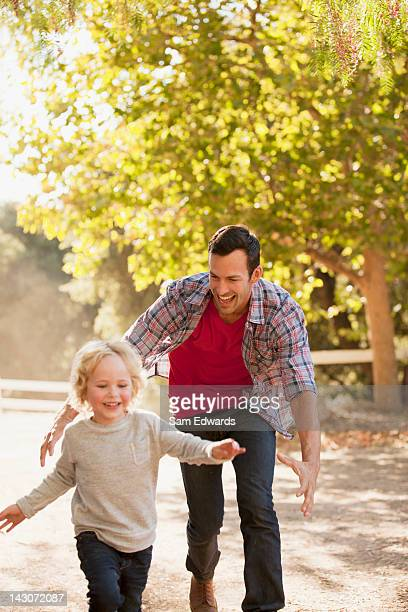 Father chasing son on dirt road