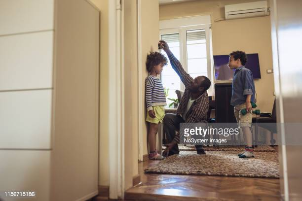 father checking height of his children - measuring stock pictures, royalty-free photos & images
