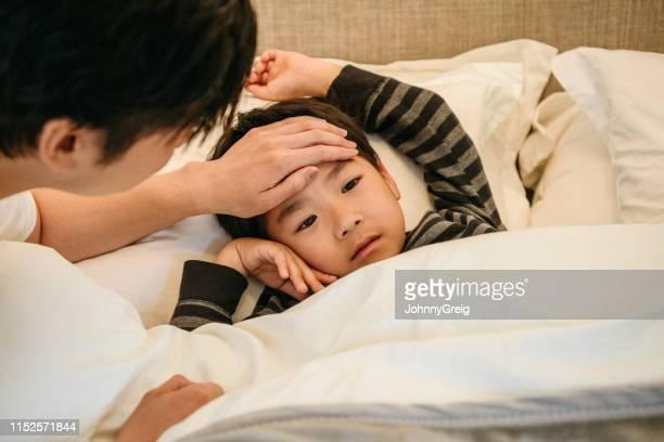 父は額に手を使って息子の体温を確認する - 病気 ストックフォトと画像