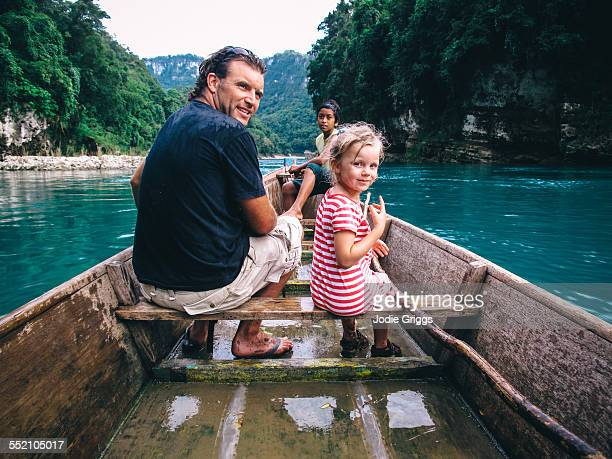 father & child riding in wooden boat down a river - leanintogether stock pictures, royalty-free photos & images