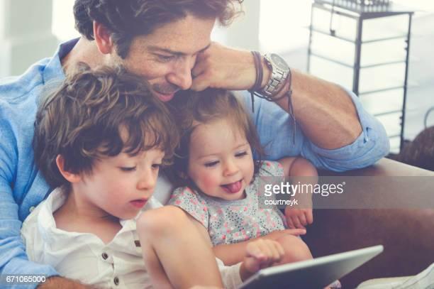 Enfants de père à l'aide d'une tablette numérique ensemble.