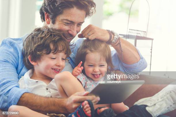 Father children using a digital tablet together.