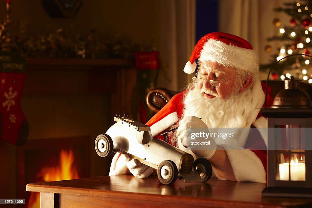 Father Christams painting a toy car in his workshop : Stock Photo