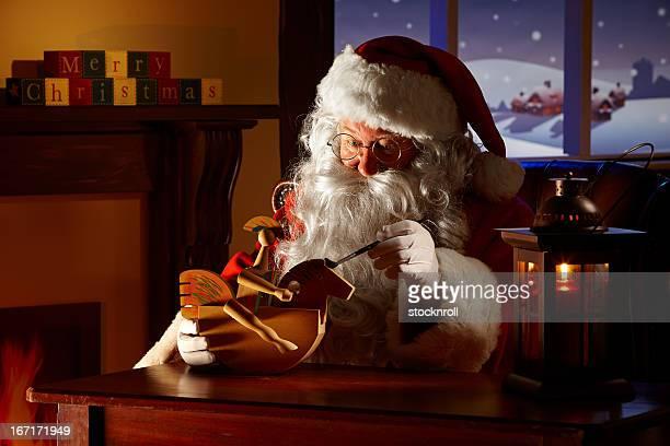 Father Christmas malen ein Spielzeug in seiner Werkstatt