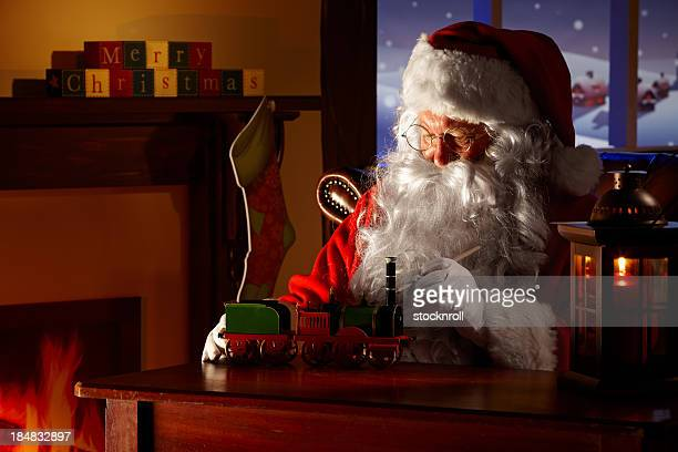 father christams painting a toy in his workshop - santas workshop stock photos and pictures