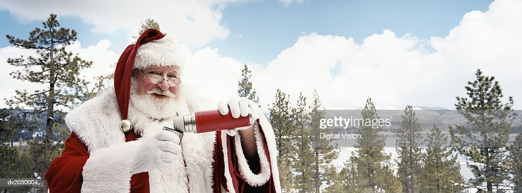 Father Christmas Drinking From a Vacuum Flask Outdoors in Winter : Stock Photo