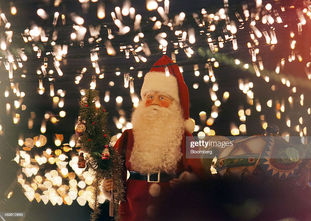 A Father Christmas figurine stands illuminated by decorative lights at a market ahead of Christmas in Berlin, Germany, on Sunday, Dec. 1, 2013. Euro-area economic growth slowed to 0.1 percent in the third quarter after a 0.3 percent gain in the previous three months. Photographer: Krisztian Bocsi/Bloomberg via Getty Images