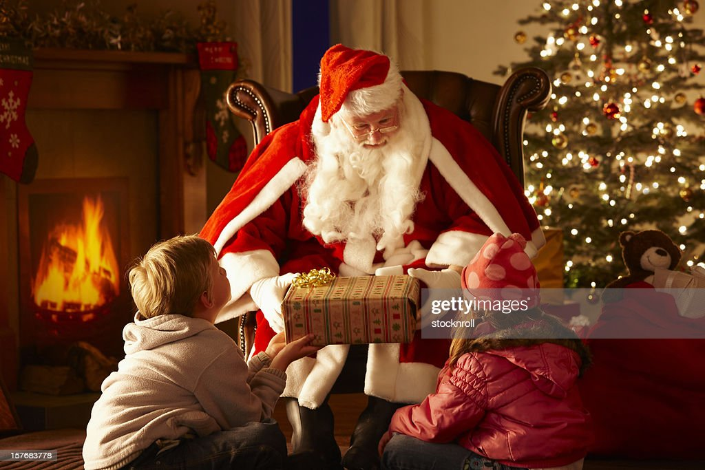 Father Christmas giving gift to children in grotto : Stock Photo