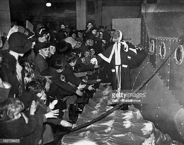 Father Christmas greeting children at Pontings' store in Kensington London 24 November 1934 Photograph by Tomlin Father Christmas greeting children...