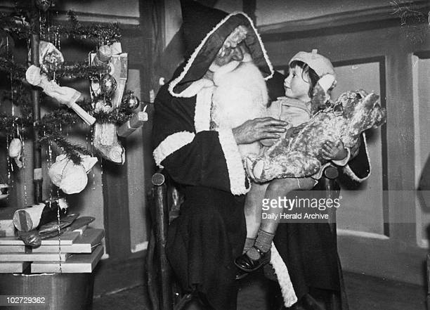 Father Christmas holding a small child 15 November 1937 Father Christmas at Arding and Hobbs' store at Clapham Junction in London The small child is...
