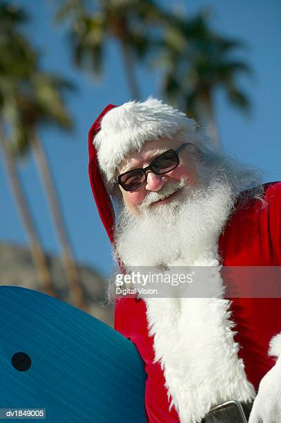Father Christmas Holding a Surf Board with Palm Trees in the Background