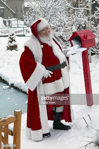 Father Christmas in a Garden Collecting Mail from a Mail Box
