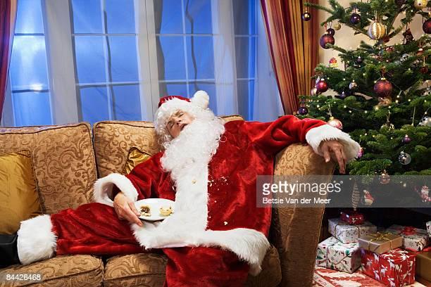 Father christmas is sleeping on sofa.