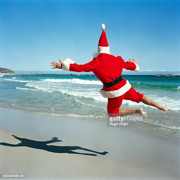 Father Christmas jumping on beach, rear view