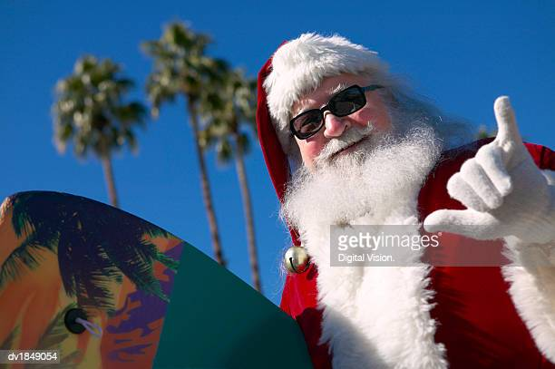 Father Christmas on Holiday Holding a Surfboard