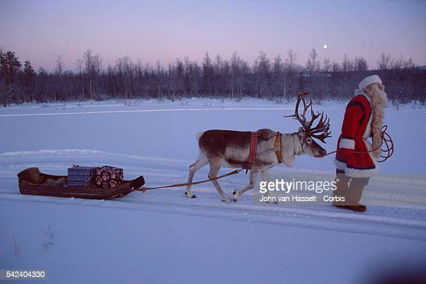 Father Christmas riding his sleigh through snow covered landscape of Lapland