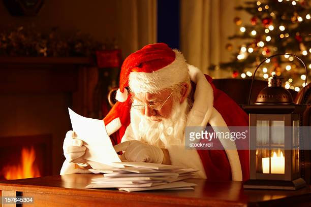 Father Christmas Sat On Chair Looking at Letters