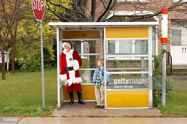Father Christmas standing at bustop, with boy (6-7)