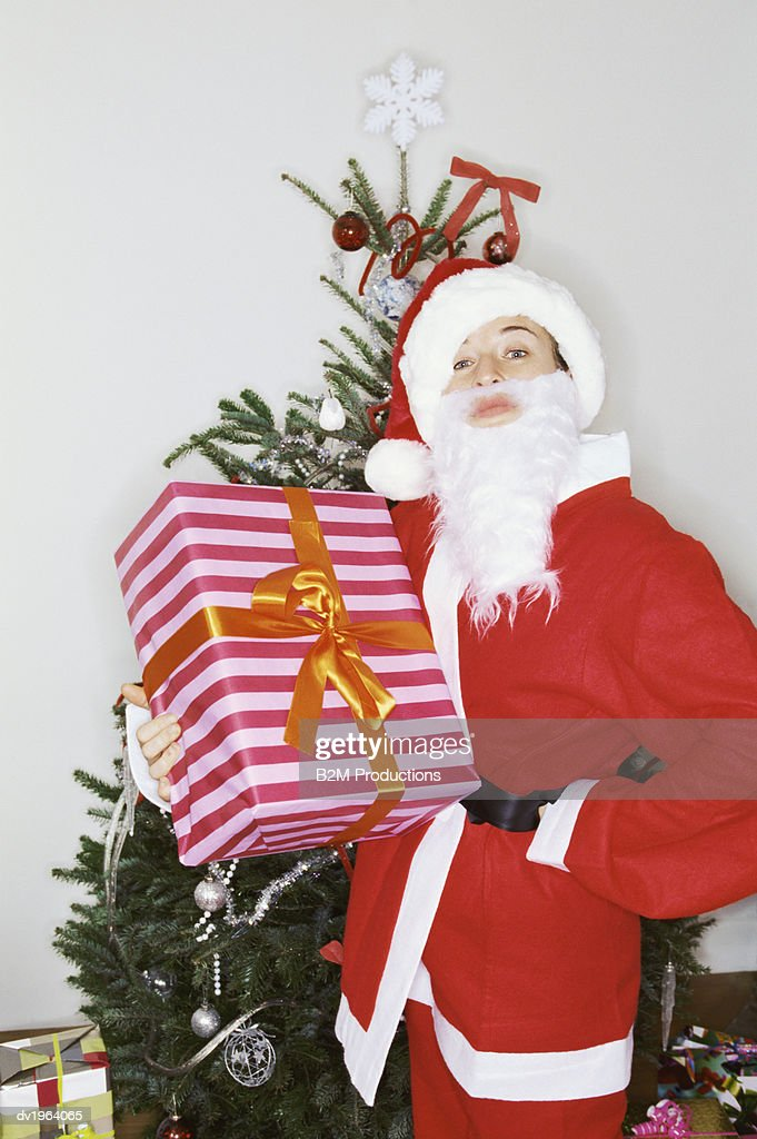 Father Christmas Stands in Front of a Christmas Tree Holding a Present : Stock Photo