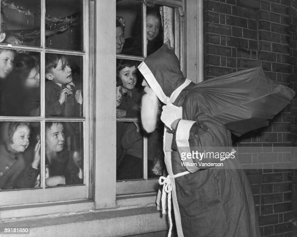 Father Christmas visits a group of children in East Ham, London, 22nd December 1950.