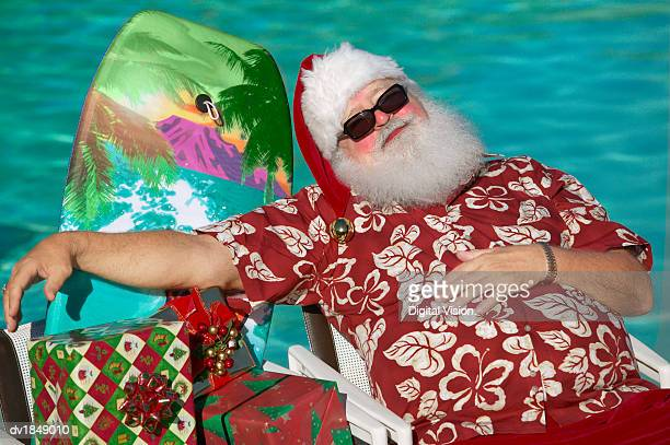 Father Christmas Wearing a Hawaiian Shirt Asleep in a Chair by a Swimming Pool