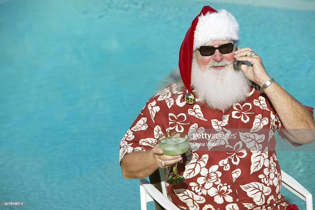 Father Christmas Wearing a Hawaiian Shirt Sitting by a Swimming Pool Holding a Mobile Phone and a Cocktail Glass : Stock Photo