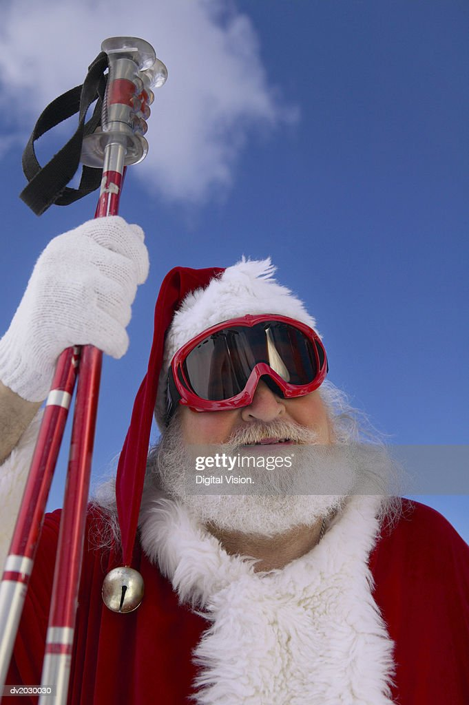 Father Christmas Wearing Skiing Goggles and Carrying Ski Poles : Stock Photo