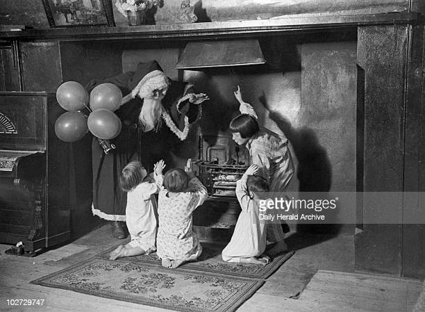 Father Christmas with children around an old fashioned fireplace 3 December 1932 Taken at the old inn 'Ye Crooked Billet' in LeighonSea Essex...