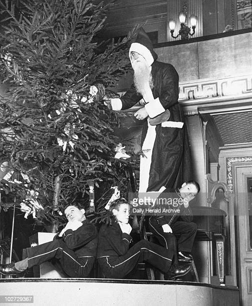 Father Christmas with page boys around a Father Christmas with page boys around a Christmas Tree 21 December 1934 Photograph by Tomlin
