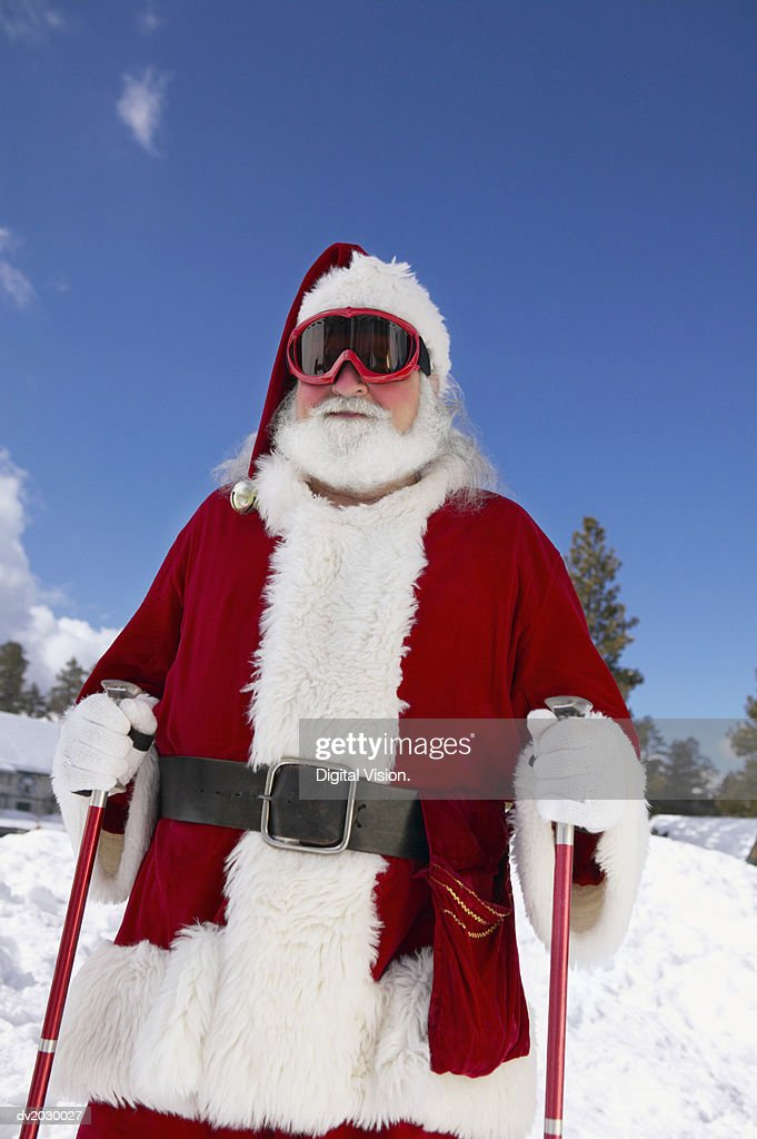 Father Christmas With Ski Poles and Goggles on a Ski Slope : Stock Photo