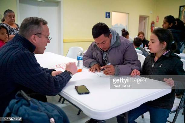 Father Christopher Williams gives name tags to Gerbin Asmar Hernandez and his daughter Annarut Hernandez at the Basilica of San Albino in Mesilla New...