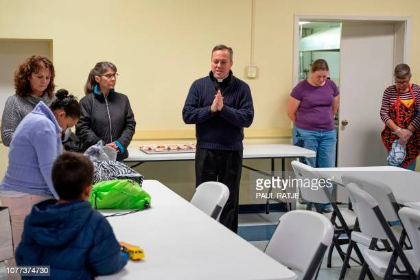 Father Christopher Williams says a blessing in the church hall of the Basilica of San Albino with a group of about 20 Central American migrants who...