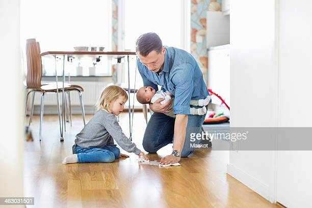 Father cleaning floor with daughter while holding baby girl at home