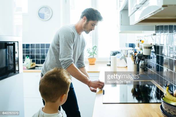 Father Cleaning Up The Kitchen After Breakfast