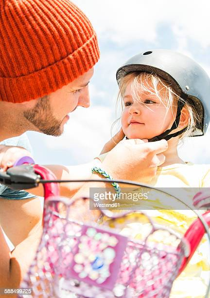 Father closing daughters helmet on bike