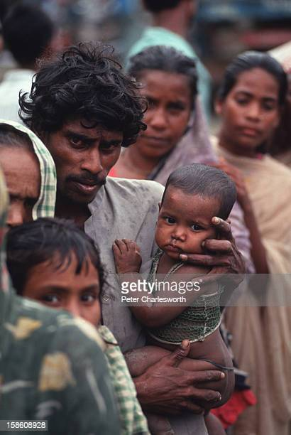 A father clutches his child as he and other villagers wait in in line for emergency relief that has finally arrived in Chittagong Food and other...