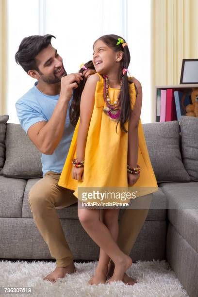 Father combing daughters hair and styling