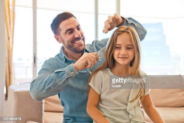 father combing his little daughter's hair at home - penteando imagens e fotografias de stock