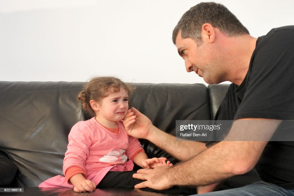 Father comforting his crying daughter : Stock Photo