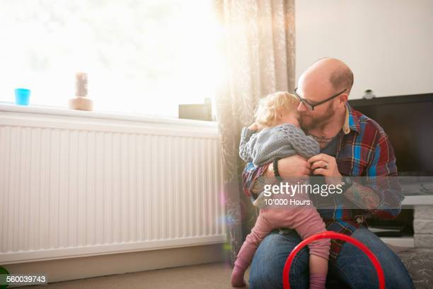 a father comforting his young daughter - radiator heater stock photos and pictures